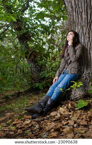 young woman talking by phone on deep forest