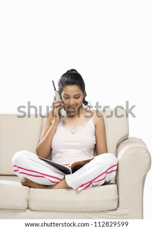 Young woman talking on a cordless phone and looking at a magazine - stock photo
