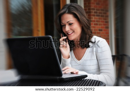 Young woman talking on cell phone and using laptop. - stock photo