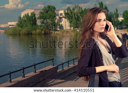 Young woman talking on her mobile phone listening to the conversation with a serious expression, she stands outdoors on granite embankment against a river backdrop, toned image, a lot of copyspace. - stock photo