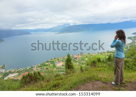 Young woman talking on mobile phone at the edge of cliff - stock photo