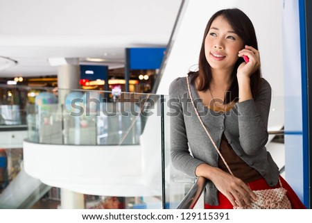 Young woman talking on mobile phone  in shopping mall - stock photo