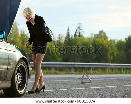 Young woman talking on mobile phone near broken car - stock photo