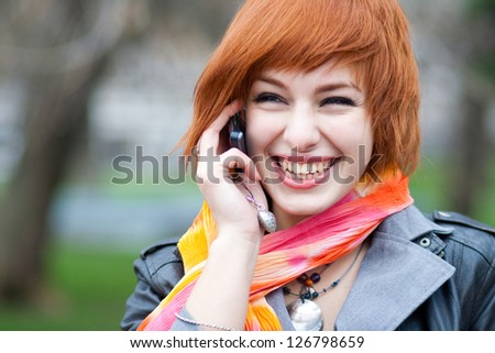 Young woman talking on mobile phone on the street - stock photo