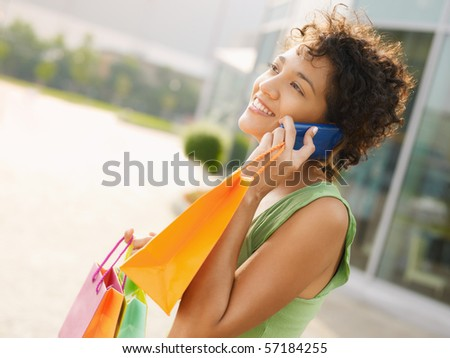 young woman talking on mobile phone out of shopping center. Horizontal shape, waist up, copy space - stock photo