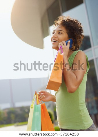 young woman talking on mobile phone out of shopping center. Vertical shape, waist up, copy space - stock photo
