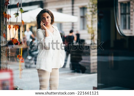 Young woman talking on phone and looking at store window
