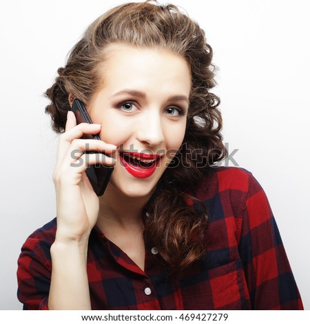 young woman talking on smartphone over white background