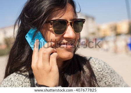 young woman talking on telephone in the beach