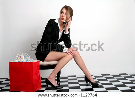 Young woman talking on the cellphone while sitting with a red bag next to her - stock photo