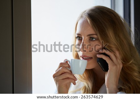 Young woman talking on the phone and drinking coffee at the window - stock photo