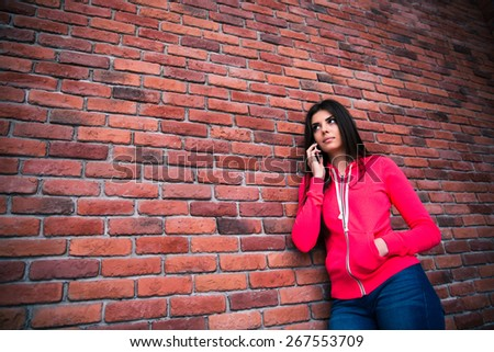 Young woman talking on the phone over brick wall and looking away