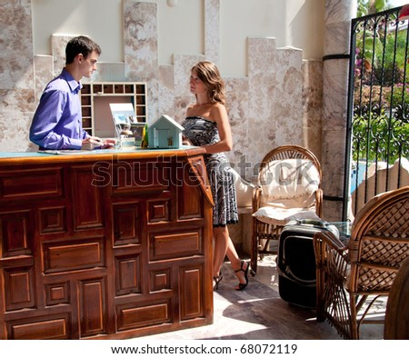 Young woman talking with hotel receptionist - stock photo