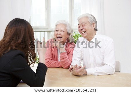 Young woman talking with senior couple	 - stock photo