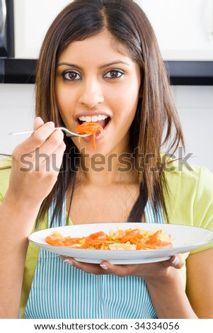 young woman tasting food in kitchen - stock photo
