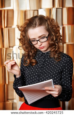 Young woman teacher checks music book.