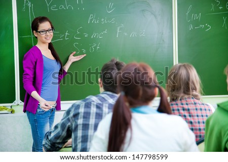 young woman-teacher conducts lessons with a group of students - stock photo