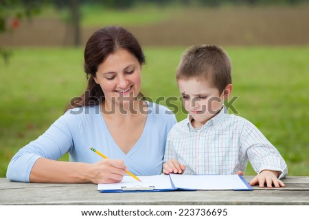 Young woman teacher teaches little young boy in white shirt writing or drawing with a pencil on a sheet of paper on wood table in the park  - stock photo