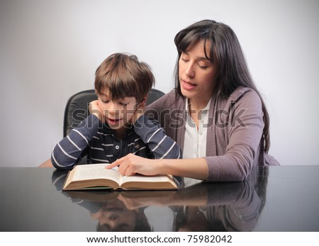 Young woman teaching a child how to read - stock photo
