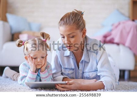 Young woman teaching her daughter at home - stock photo