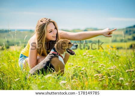 Young woman (teen girl) showing her dog with hand - outdoor in nature - stock photo