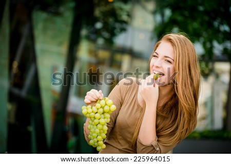 Young woman - teenage girl eating grapes outdoor in street - stock photo