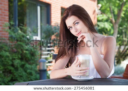 Young woman - teenage girl outdoors sitting at the cafe table with a cup of coffee and looking into the camera.  - stock photo