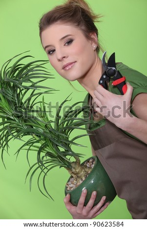 Young woman tending to her plants - stock photo