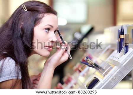 Young woman testing cosmetics - stock photo