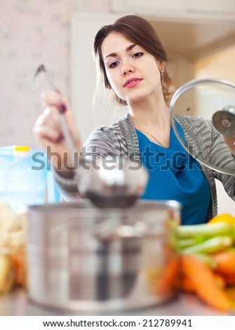 young woman tests food with ladle in the kitchen at home - stock photo