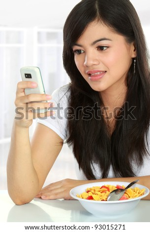 young woman text a message while having breakfast in the morning - stock photo