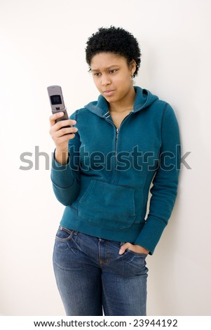 Young woman text messaging, looking surprised.