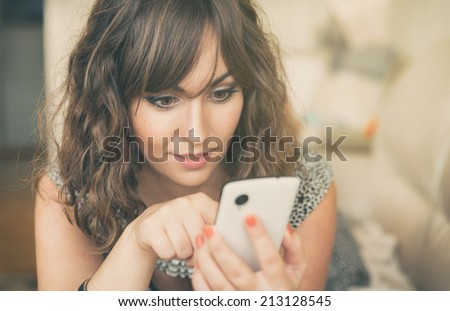 Young woman texting on her mobile phone iphon style concentrating as she enters data on the touchscreen with her finger in a communication concept - stock photo