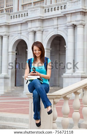 young woman texting on school campus - stock photo