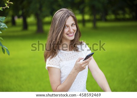 Young Woman texting on the smart phone walking in the summer park