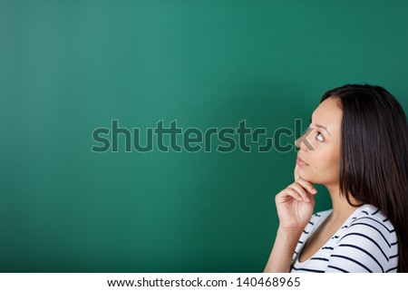 young woman thinking about something looking on blackboard - stock photo