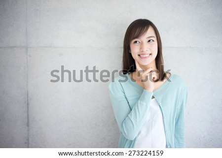 young woman thinking against concrete wall - stock photo