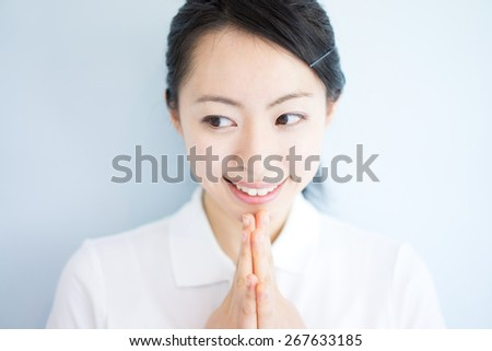 young woman thinking, against light blue background - stock photo
