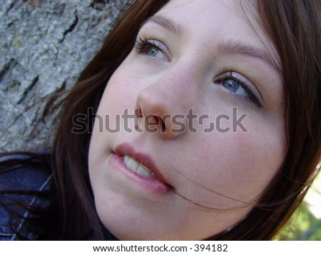 Young woman thinking and biting her bottom lip