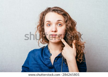 young woman thinking, daydreaming deeply about something hand on chin looking up - stock photo