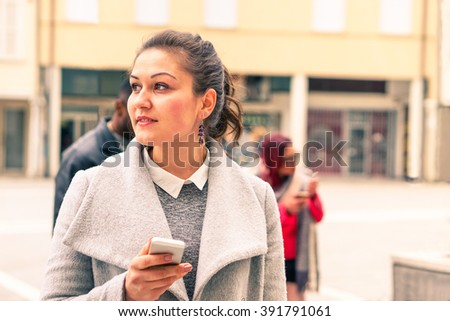 Young woman thinking face with mobile phone is standing on the street -  Portrait of thoughtful girl holding mobile - Concept of modern technology device and human moods - Tones of a cloudy bright day - stock photo
