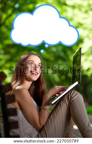 Young woman thinking, having idea wihle typing something in laptop at the park. Text cloud over her head - stock photo