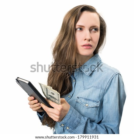Young woman thinking of spending or saving money. Troubled woman holding money and looking to the side, sideways. copy space - stock photo