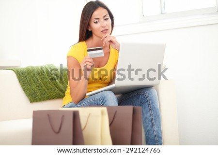 Young woman thinking to buy with credit card and laptop while sitting inside the house - stock photo