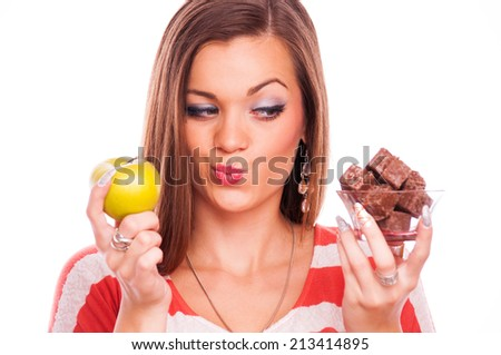 Young woman thinking what to eat first - looking on the chocolate wafer - stock photo