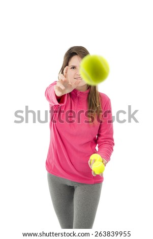 Young woman throwing a tennis ball against a white background - stock photo
