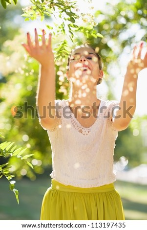 Young woman throwing little leafs - stock photo