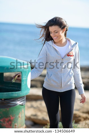 Young Woman Throwing Paper In Garbage Bin; Outdoors - stock photo