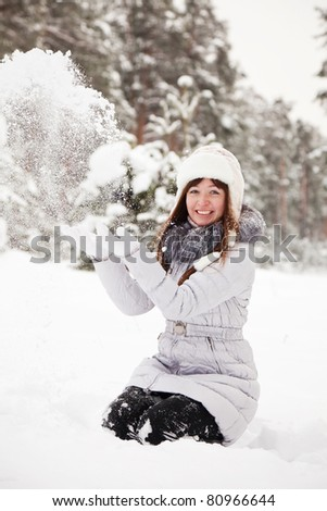 young woman throwing snow  in the air in park - stock photo