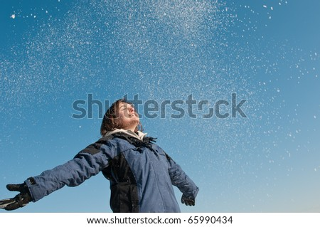 Young woman throwing snow on blue sky in background - joy and happines emotions - stock photo